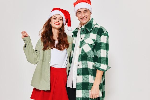 Wesoły mężczyzna i kobieta stoją obok czapek wigilijnych wakacje