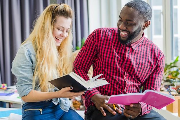 Wesoły mężczyzna i kobieta z książkami