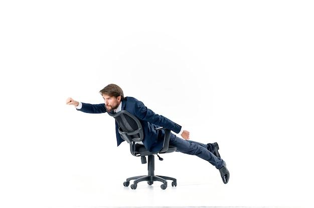 Wesoły mężczyzna jeździ w studiu kierownika biura na krześle