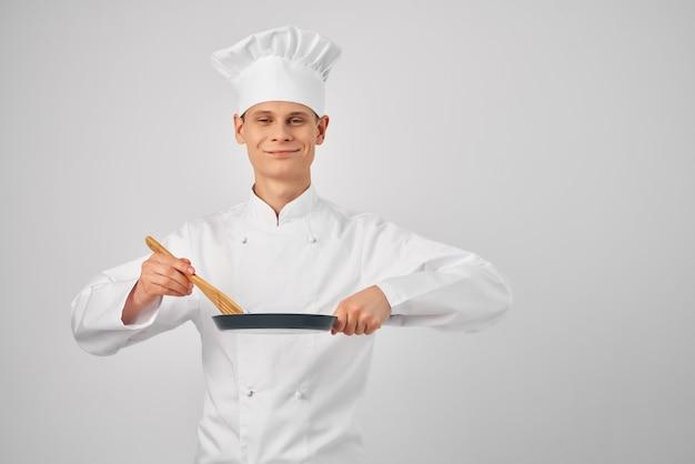 Wesoły mężczyzna kucharz z patelnią w dłoniach pracuje nad gotowaniem