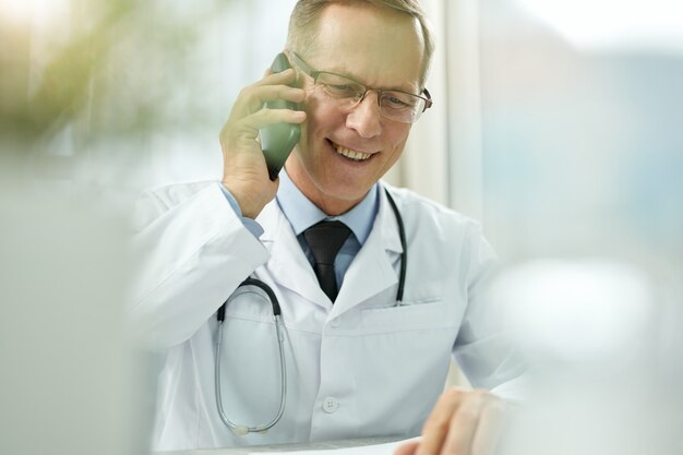 Wesoły mężczyzna lekarz rozmawia przez telefon komórkowy w klinice