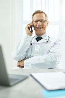 Wesoły mężczyzna lekarz rozmawia przez telefon komórkowy w pracy