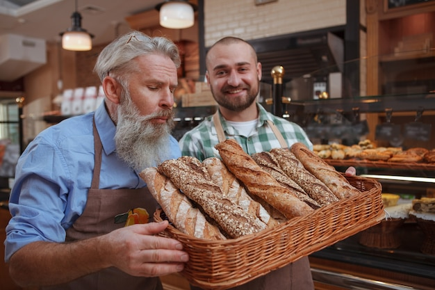Wesoły mężczyzna piekarz pokazujący starszemu ojcu świeżo upieczony chleb w koszu