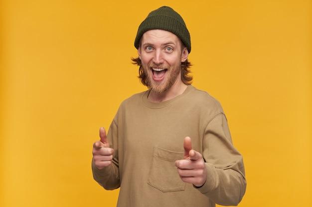 Wesoły mężczyzna, pozytywny facet o blond włosach, brodzie i wąsach. ubrana w zieloną czapkę i beżowy sweter. wskazuje na ciebie palcami i uśmiecha się. pojedynczo na żółtej ścianie