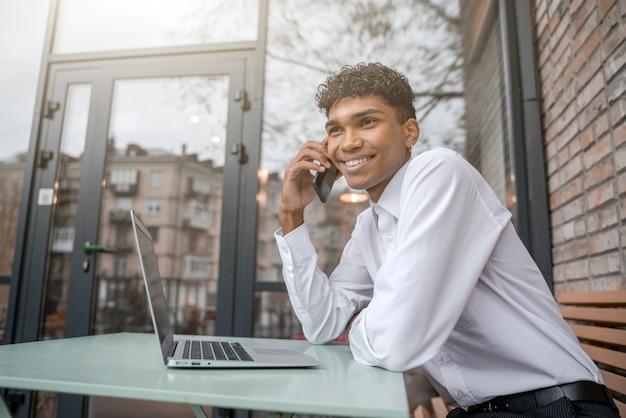 Wesoły mężczyzna pracuje przy laptopie i rozmawia przez telefon. czarny facet siedzi na letnim tarasie lub werandzie w pobliżu ceglanego muru. widok na wiosenne centrum biznesowe.