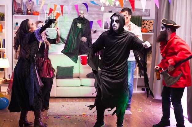 Wesoły mężczyzna przebrany za kostucha z ruchami tanecznymi na imprezie z okazji halloween.