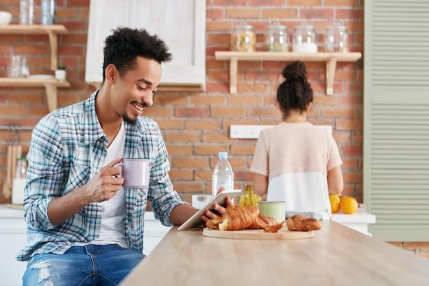 Wesoły mężczyzna rasy mieszanej ogląda komedię na tablecie, korzysta z bezpłatnego łącza internetowego, pije kawę