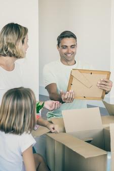 Wesoły mężczyzna rozpakowujący rzeczy z żoną i dziećmi w nowym mieszkaniu, siedzący na podłodze w pobliżu otwartych pudeł