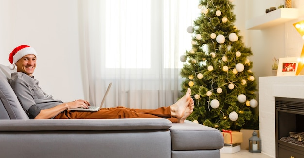 Wesoły mężczyzna siedzący na kanapie i używający laptopa w pobliżu choinki w domu