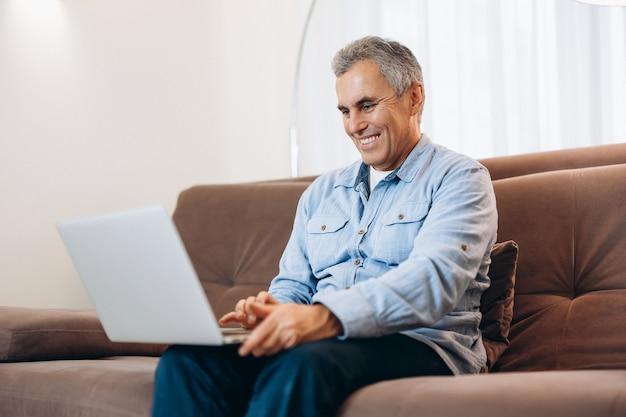 Wesoły mężczyzna siedzi na kanapie, za pomocą laptopa w domu w przytulnym salonie. zwyczajny styl. mężczyzna w średnim wieku czyta maile, uśmiecha się i odpowiada na nie. koncepcja nowoczesnej technologii. człowiek czyta dobre wieści w sieci.