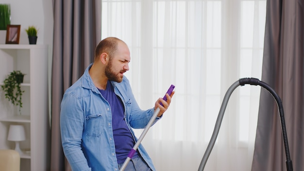 Wesoły mężczyzna śpiewający na mopie i sprzątający swój pokój