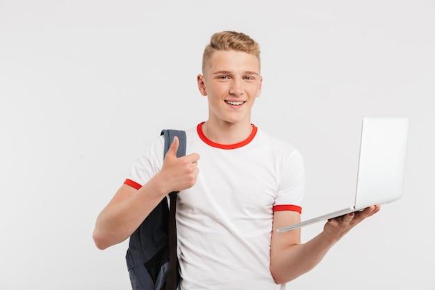 Wesoły mężczyzna student na sobie koszulkę i plecak pokazując kciuk do góry, trzymając otwarty laptop na białym tle