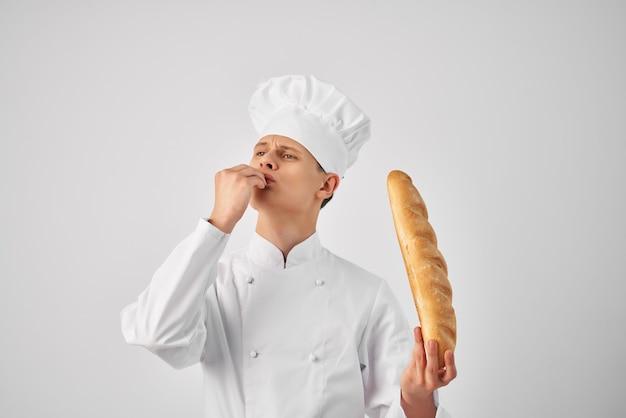 Wesoły mężczyzna szef kuchni trzymający bochenek jedzenia w restauracji