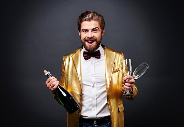 Wesoły mężczyzna trzyma butelkę szampana i flet szampana