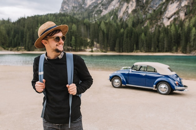 Wesoły mężczyzna trzyma swój plecak i pozuje z uśmiechem stojąc przed pięknym jeziorem w górach