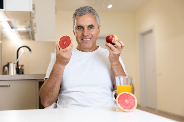 Wesoły mężczyzna trzymający jabłko i grejpfrut blisko twarzy i uśmiechnięty