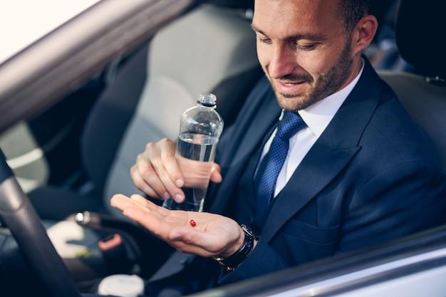 Wesoły mężczyzna trzymający uśmiech na twarzy, czujący się lepiej po zażyciu leku, będąc w samochodzie