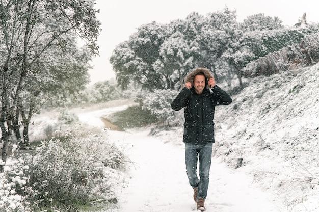 Wesoły mężczyzna ubrany w ciepłą kurtkę idąc ścieżką w lesie podczas opadów śniegu w zimie i patrząc na kamery