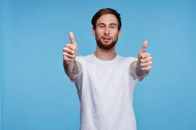 Wesoły mężczyzna w białej koszulce tatuaż na ramionach przycięty widok mody