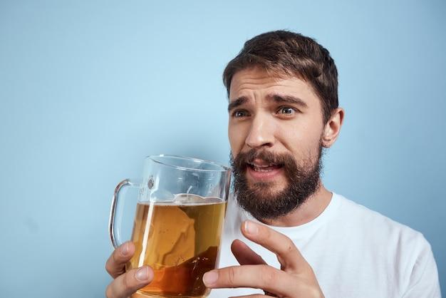 Wesoły mężczyzna w białej koszulce z kuflem piwa pijany na niebiesko