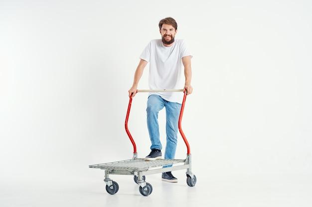 Wesoły mężczyzna w białym t-shirt transport w polu jasnym tle. zdjęcie wysokiej jakości