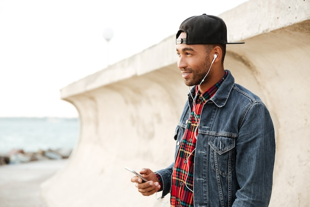 Wesoły mężczyzna w czapce spacerujący po plaży i rozmawiający przez telefon podczas słuchania muzyki przez słuchawki