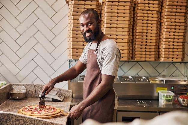Wesoły mężczyzna w fartuchu patrzący w kamerę i uśmiechający się podczas krojenia pizzy okrągłym kółkiem tnącym