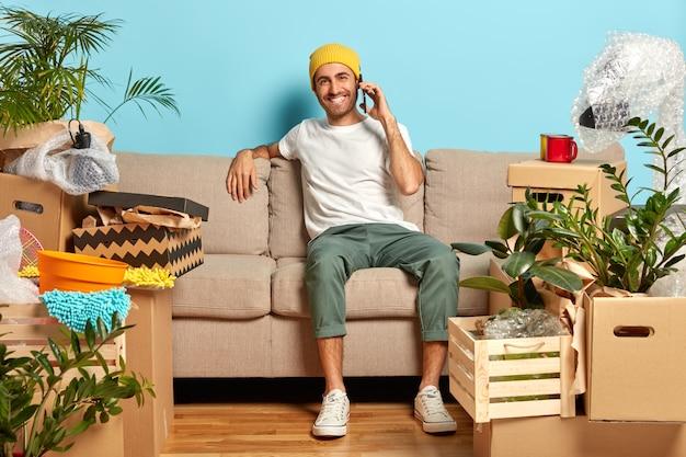 Wesoły mężczyzna w modnych ubraniach siedzi na kanapie