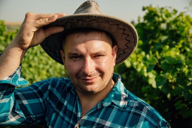 Wesoły mężczyzna w nowoczesnym kapeluszu młodego winiarza znajduje się w winnicy portret winiarza wygląda...