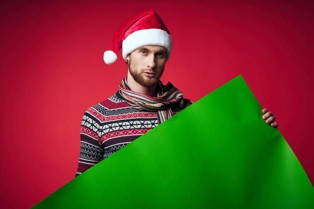 Wesoły mężczyzna w santa hat trzyma transparent wakacje czerwone tło