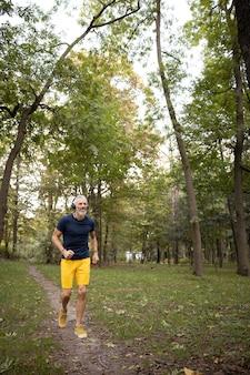 Wesoły mężczyzna w słuchawkach biegający w lesie