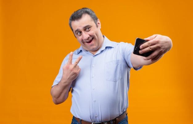 Wesoły mężczyzna w średnim wieku na sobie niebieską koszulę w pionowe paski, śmiejąc się i biorąc selfie na smartfonie