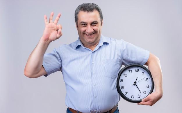 Wesoły mężczyzna w średnim wieku w niebieskiej koszuli w pionowe paski, trzymając duży zegar robi ok znak palcami