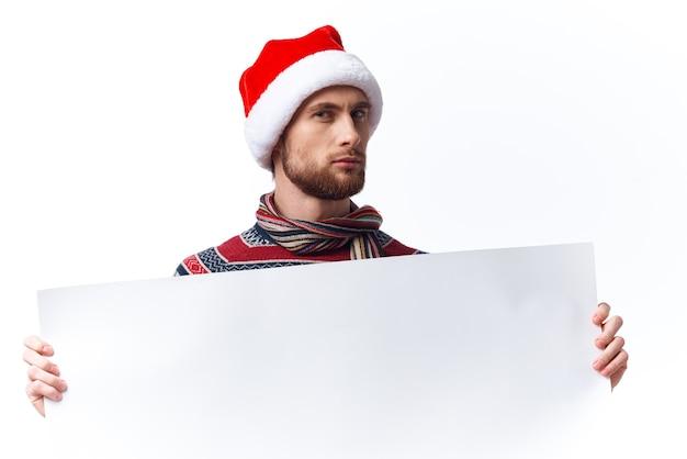 Wesoły mężczyzna w świątecznym kapeluszu z białym plakatem makieta boże narodzenie na białym tle