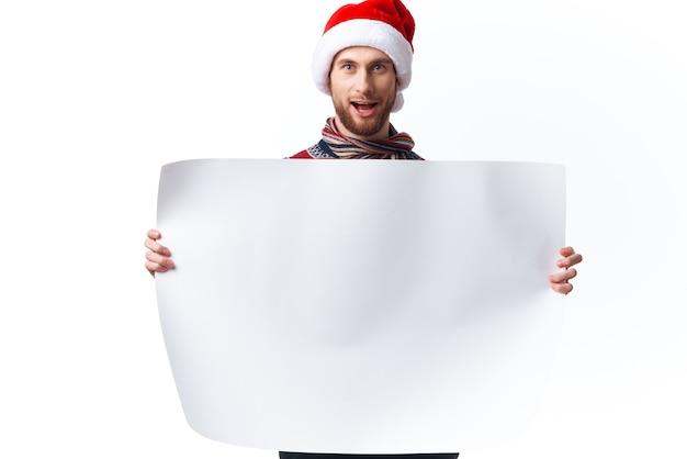 Wesoły mężczyzna w świątecznym kapeluszu z białym plakatem makiety świąteczne studio copyspace
