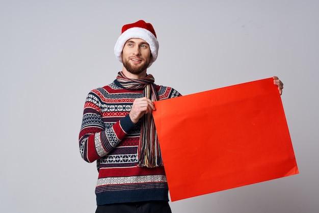 Wesoły mężczyzna w świątecznym kapeluszu z czerwonym plakatem makieta jasnym tłem