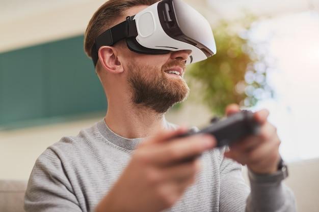 Wesoły mężczyzna w zestawie słuchawkowym vr korzystającym z interaktywnej gry wideo