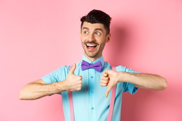 Wesoły mężczyzna wyglądający na szczęśliwego w lewo, pokazujący kciuki w dół, oceniający produkt, udzielający pozytywnych i negatywnych opinii, stojący na różowym tle.