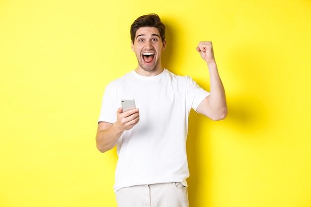 Wesoły mężczyzna wygrywający na smartfonie, podnoszący rękę do góry i trzymający telefon komórkowy, osiągający cel aplikacji, stojący nad żółtym tłem