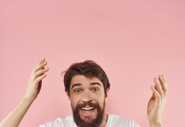 Wesoły mężczyzna z brodą z białym tshirt różowym tle