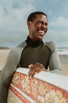 Wesoły mężczyzna z deską surfingową na plaży