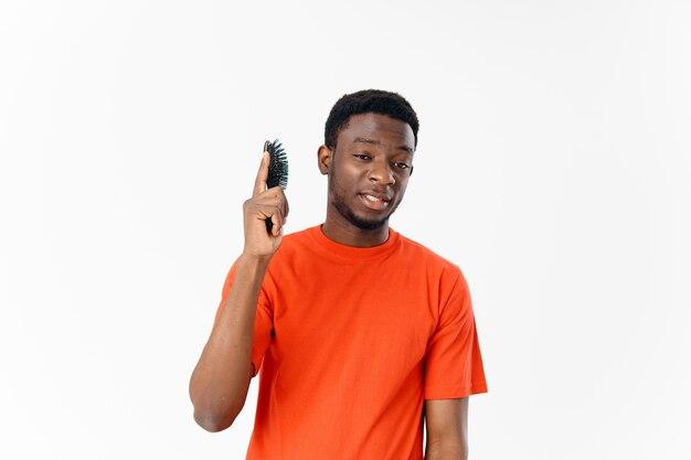Wesoły mężczyzna z grzebieniem w dłoniach pielęgnacja włosów afro fryzura