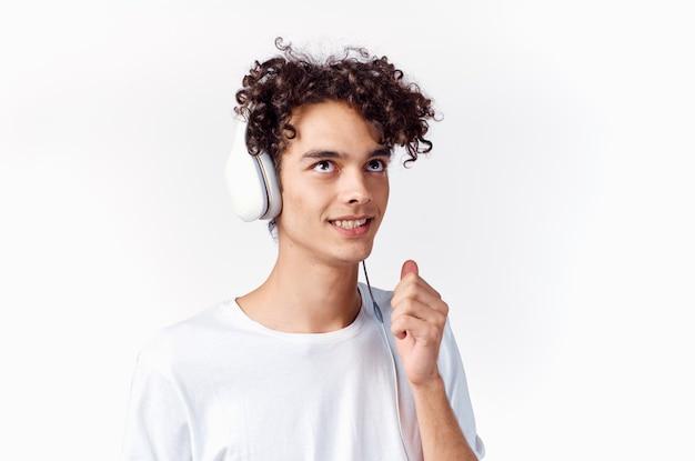 Wesoły mężczyzna z kręconymi włosami w słuchawkach słucha muzycznych emocji. wysokiej jakości zdjęcie