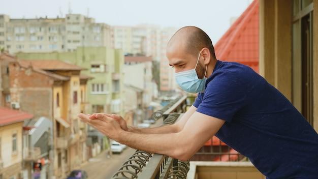 Wesoły mężczyzna z maską klaszczącą na balkonie na poparcie lekarza w walce z koronawirusem.