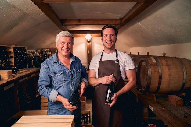Wesoły mężczyźni rasy kaukaskiej uśmiechający się radośnie, stojąc w piwnicy z nieoznakowanymi butelkami wina. beczki na tle