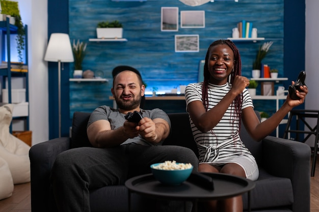 Wesoły międzyrasowy ludzie wygrywający grę wideo w telewizji