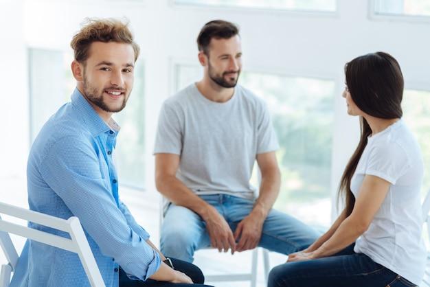 Wesoły miły młody człowiek uśmiechnięty i mający dobry nastrój podczas wizyty w grupie psychologicznej