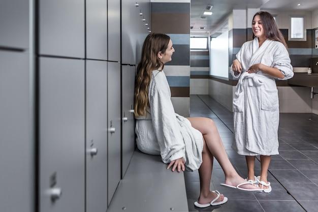 Wesoły młode kobiety na czacie w salonie spa