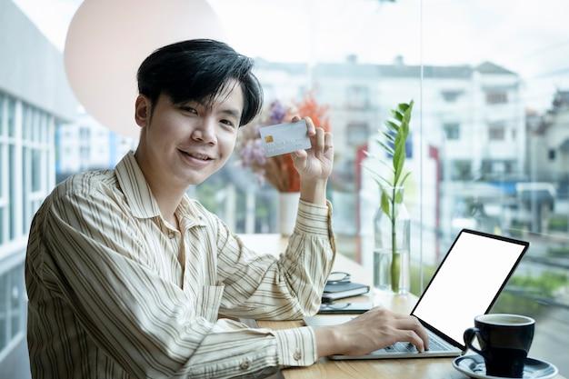 Wesoły młody azjatycki człowiek posiadający kartę kredytową i uśmiechając się do kamery.