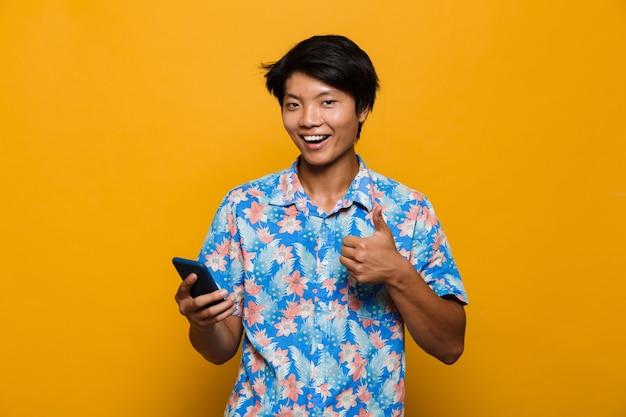 Wesoły młody azjatycki człowiek stojący na białym tle nad żółtą przestrzenią za pomocą telefonu komórkowego, pokazując kciuk do góry.